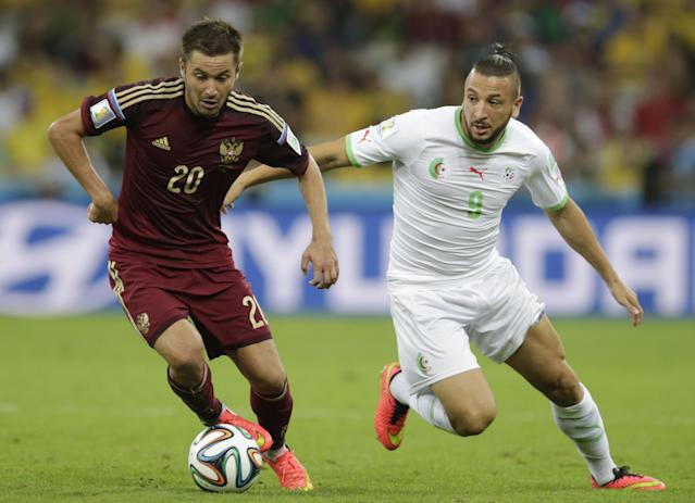 Russia's Victor Faizulin (L) fights for the ball with Algeria's Nabil Ghilas during their 2014 World Cup Group H soccer match at the Baixada arena in Curitiba June 26, 2014. REUTERS/Henry Romero (BRAZIL - Tags: SOCCER SPORT WORLD CUP)