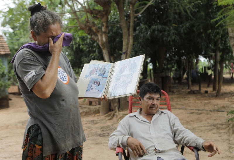 """In this Nov. 14, 2012 photo, Lidia Romero cries holding a family photo album as her husband Catalino Aguero talks in their home's yard in the Carro Cue settlement, near Curuguaty, Paraguay. The couple's son De Los Santos was killed and their daughter Lucia was imprisoned during the """"Massacre of Curuguaty"""" on June 15 when negotiations between farmers occupying a rich politician's land ended with a barrage of bullets that killed 11 farmers and 6 police officers. """"They gave me my son's decomposing body in a black plastic bag. He had bullet wounds in both feet, but a huge hole in his neck,"""" said Catalino Aguero. (AP Photo/Jorge Saenz)"""