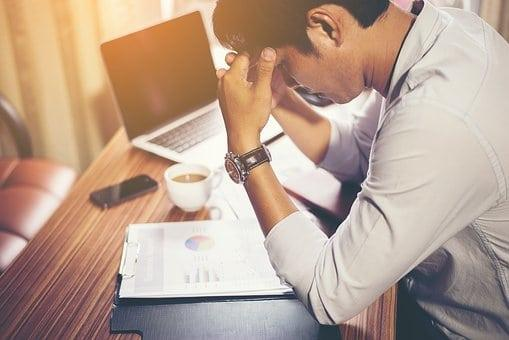 Man hunched over notepad at wooden desk
