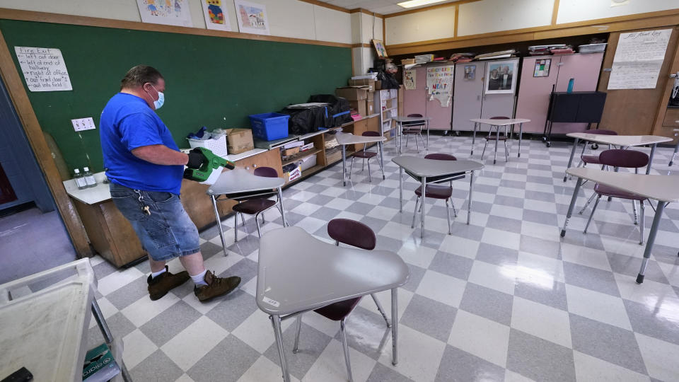 Jimmy Manijak uses a handheld disinfecting electrostatic sprayer while cleaning classroom desks at the E.N. White School in Holyoke, Mass., on Wednesday, Aug. 4, 2021. Schools across the U.S. are about to start a new year amid a flood of federal money larger than they've ever seen before, an infusion of pandemic relief aid that is four times the amount the U.S. Department of Education sends to K-12 schools in a typical year. (AP Photo/Charles Krupa)