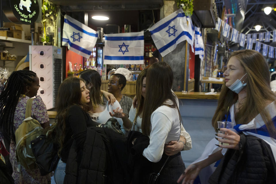 Israeli women celebrate Independence Day at a bar in the Mahane Yehuda Market in Jerusalem, after more than a year of coronavirus restrictions, Wednesday, April 14, 2021. (AP Photo/Maya Alleruzzo)