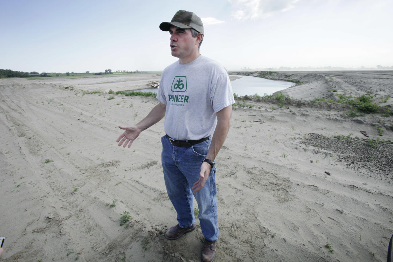 In this photo taken May 22, 2012, farmer Mason Hansen talks about the damage in his sand-covered farm field in Missouri Valley, Iowa. Hundreds of farmers in Iowa and Nebraska are still struggling to remove sand and fill holes gouged by the Missouri River, which swelled last summer with rain and snowmelt and overflowed onto thousands of acres of farmland. (AP Photo/Charlie Neibergall)