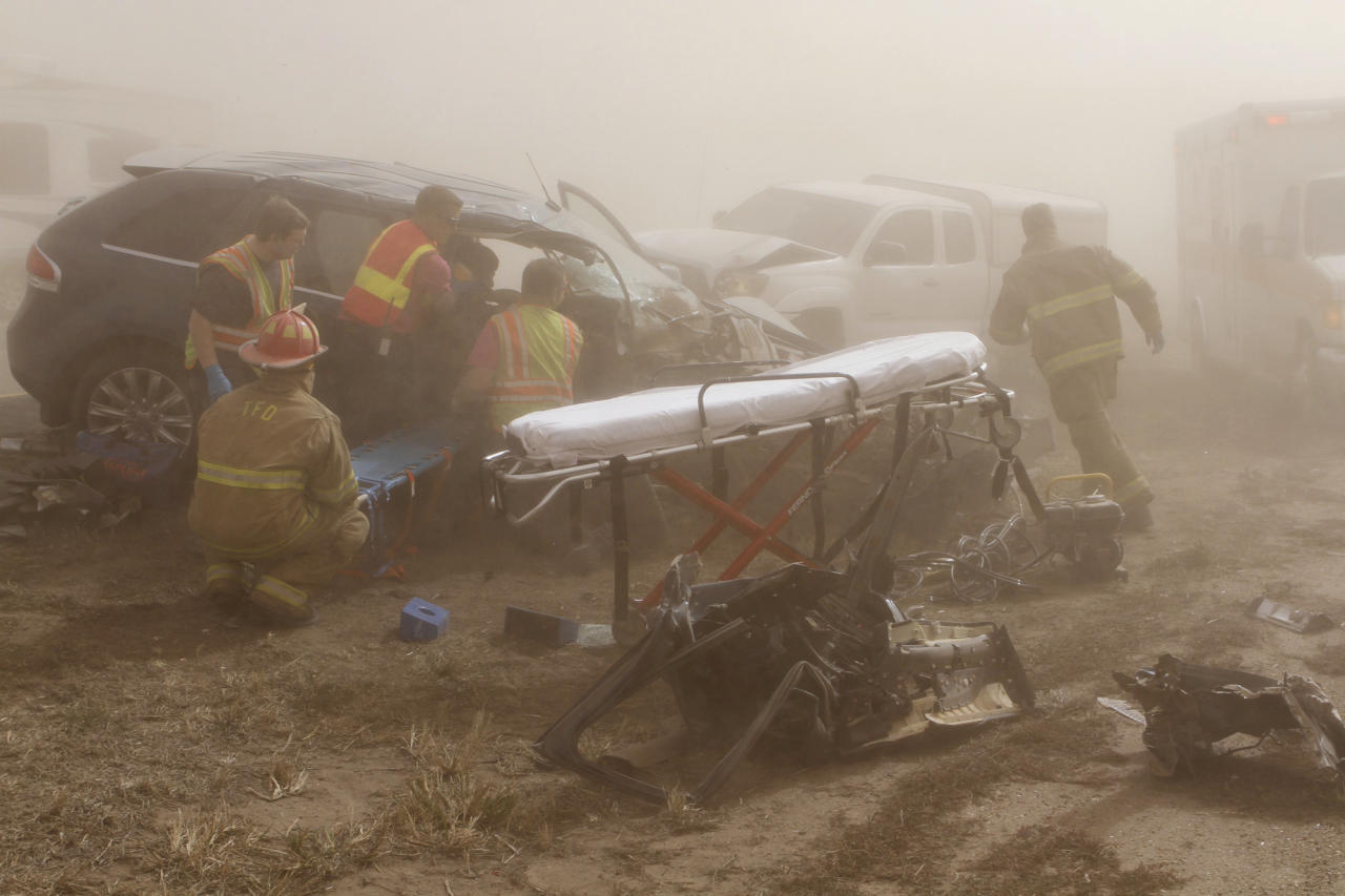 Rescue personnel work to remove a woman pinned in a vehicle after it was involved in an accident on Interstate 35 near Blackwell, Okla., Thursday, Oct. 18, 2012 A massive dust storm swirling reddish-brown clouds over northern Oklahoma triggered a multi-vehicle accident, forcing police to shut down the heavily traveled roadway amid near blackout conditions. The highway patrol said the dust storm caused a multi-car accident, and local police said nearly three dozen cars and tractor-trailers were involved. Blackwell Police Chief Fred LeValley said nine people were injured, but there were no fatalities. (AP Photo/The Ponca City News, Rolf Clements)