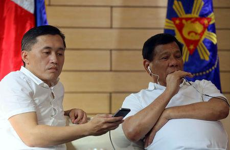 Philippine President Rodrigo Duterte speaks with China's President Xi Jinping over the phone while with Christopher 'Bong' Go, Special Assistant to the President, in Davao City