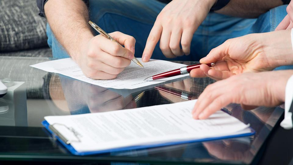 man signing paper for power of attorney