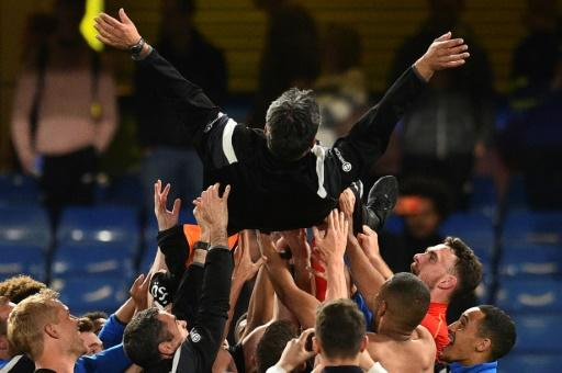 High life: Huddersfield Town coach David Wagner is thrown in the air by his players and staff