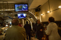 People watch Spanish TV channel with the breaking news of late Spanish dictator Francisco Franco's exhumation, on the screen, in the basque city of Vitoria, northern Spain, Thursday, Oct. 24 2019. Forty-four years after his demise, the remains of Spanish dictator Gen. Francisco are to be dug out of his grandiose resting place outside Madrid and taken to a small family crypt, finally satisfying a long-standing demand of his victims' relatives and others who suffered under his regime. (AP Photo/Alvaro Barrientos)
