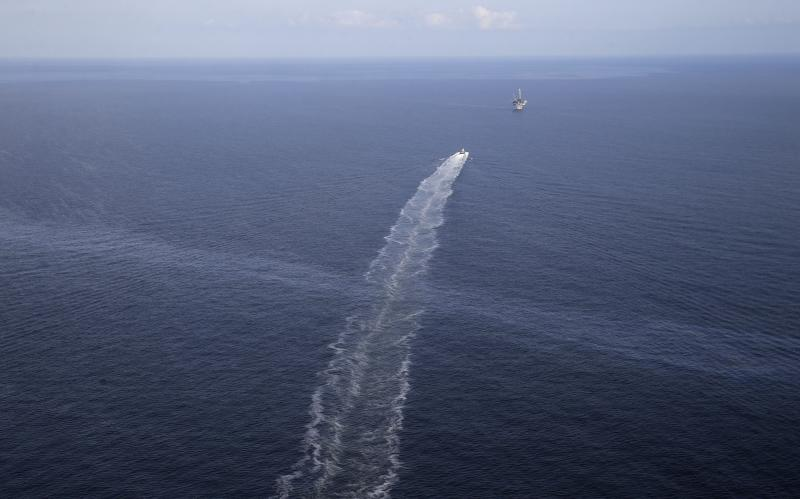 FILE- In this March 31, 2015 aerial photo, the wake of a supply vessel heading towards a working platform crosses over an oil sheen drifting from the site of the former Taylor Energy oil rig in the Gulf of Mexico, off the coast of Louisiana. A new federally led estimate of oil seeping from a platform toppled off Louisiana 14½ years ago is below other recent estimates. But the report contradicts the well owner's assertions about the amount and source of oil. Oil and gas have been leaking into the Gulf of Mexico since a subsea mudslide caused by Hurricane Ivan on Sept. 15, 2004 knocked over a Taylor Energy Co. production platform. (AP Photo/Gerald Herbert, File)