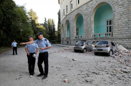 Police officers secure the area next to destroyed cars and a damaged building after an earthquake in Tirana