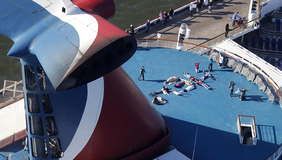 """Passengers spell out the word """"HELP"""" aboard the disabled Carnival Lines cruise ship Triumph as it is towed to harbor off Mobile Bay, Ala., Thursday, Feb. 14, 2013. The ship with more than 4,200 passengers and crew members has been idled for nearly a week in the Gulf of Mexico following an engine room fire. (AP Photo/Gerald Herbert)"""