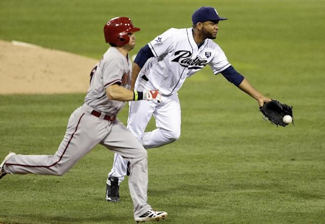 San Diego Padres starting pitcher Odrisamer Despaigne, right, gloves the ball to first baseman Yasmani Grandal as Arizona Diamondbacks' Ender Inciarte, left, can't reach the base in time during the third inning of a baseball game Tuesday, Sept. 2, 2014, in San Diego. (AP Photo/Gregory Bull)