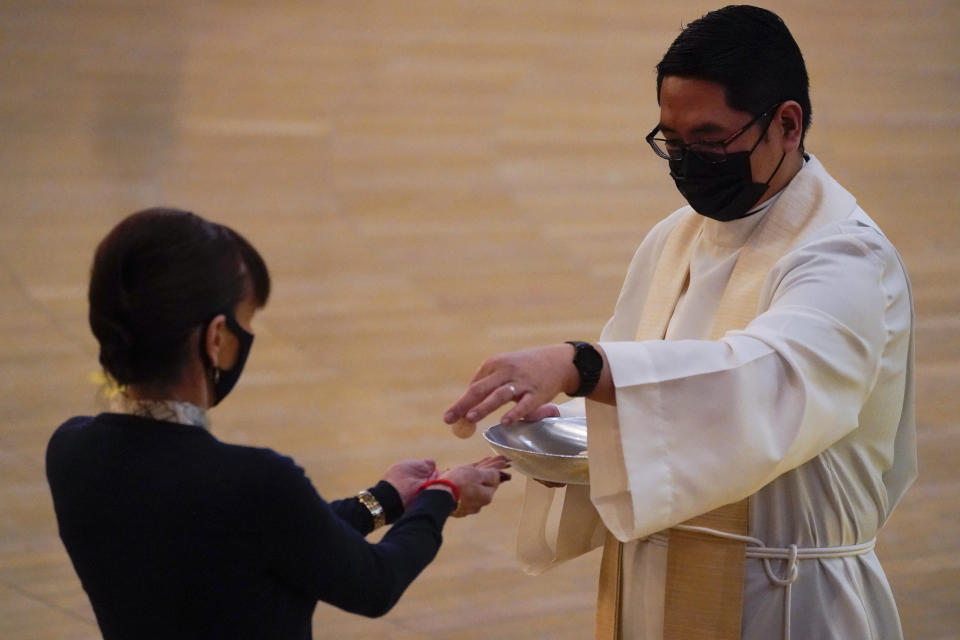 A woman receives communion during a Christmas Eve Mass inside the Cathedral of Our Lady of the Angels Thursday, Dec 24, 2020, in Los Angeles. California became the first state to record 2 million confirmed coronavirus cases, reaching the milestone on Christmas Eve as nearly the entire state was under a strict stay-at-home order and hospitals were flooded with the largest crush of cases since the pandemic began. (AP Photo/Ashley Landis)