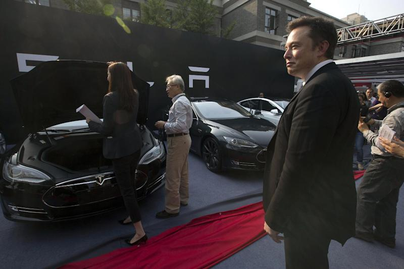 Tesla Motors CEO Elon Musk, right, looks on as a set of Tesla Model S sedans are delivered to its first customers in China at an event in Beijing, China, Tuesday, April 22, 2014. Tesla Motors delivered its first eight electric sedans to customers in China on Tuesday and Musk said the company will build a nationwide network of charging stations and service centers as fast as it can. (AP Photo/Ng Han Guan)