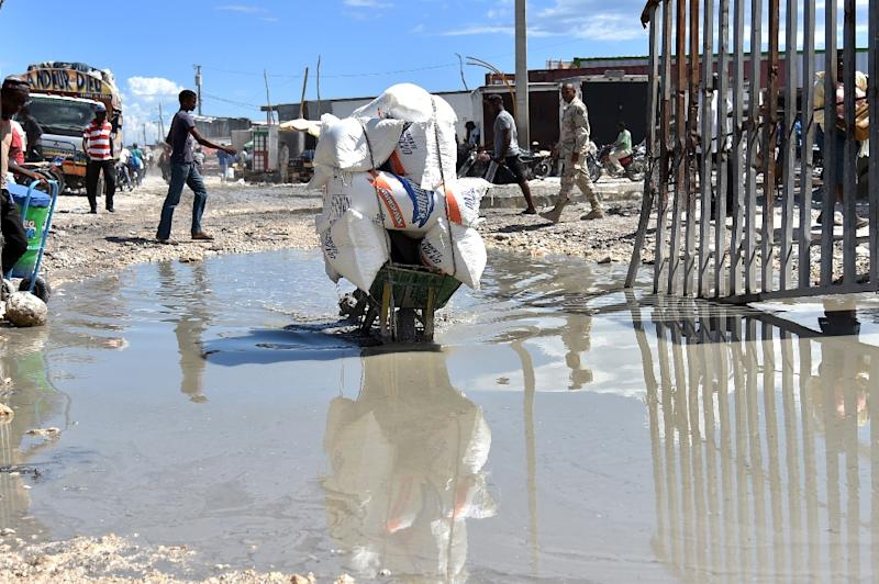 A young man passes through the Haitian-Dominican border, in Malpasse while transporting products in a wheelbarrow (AFP Photo/Hector Retamal)