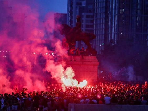 Liverpool fans let off flares outside the Liver Building in Liverpool (PA)