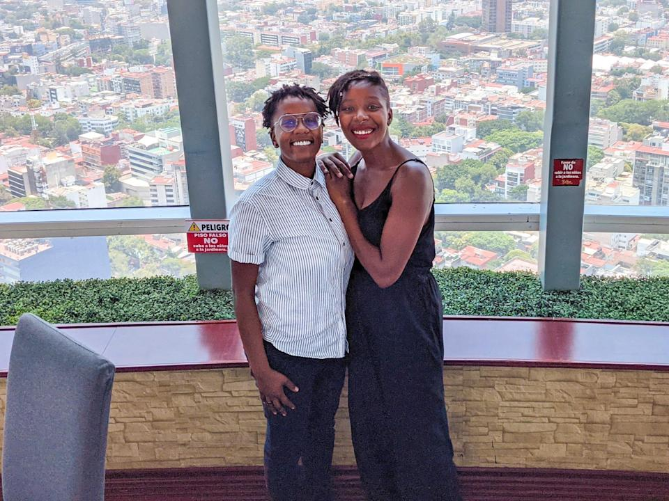 Amber and her partner posing in front of an impressive aerial building view