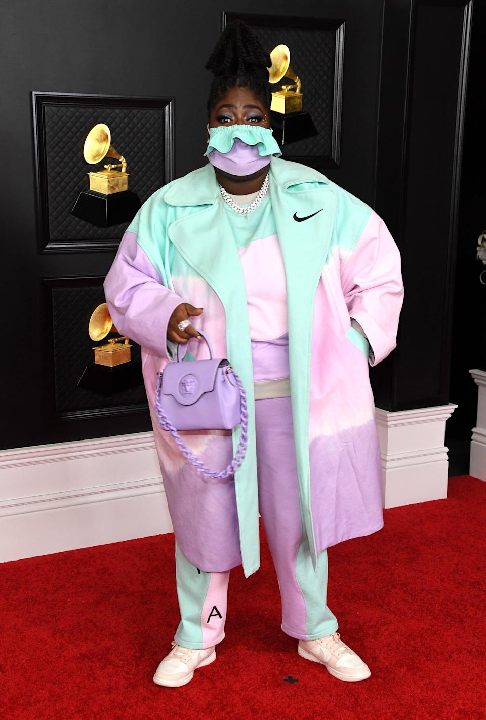 <p>Chika's custom color-blocked Nike x Meals set and matching mask with a lavender Versace handbag on the Grammys red carpet.</p>
