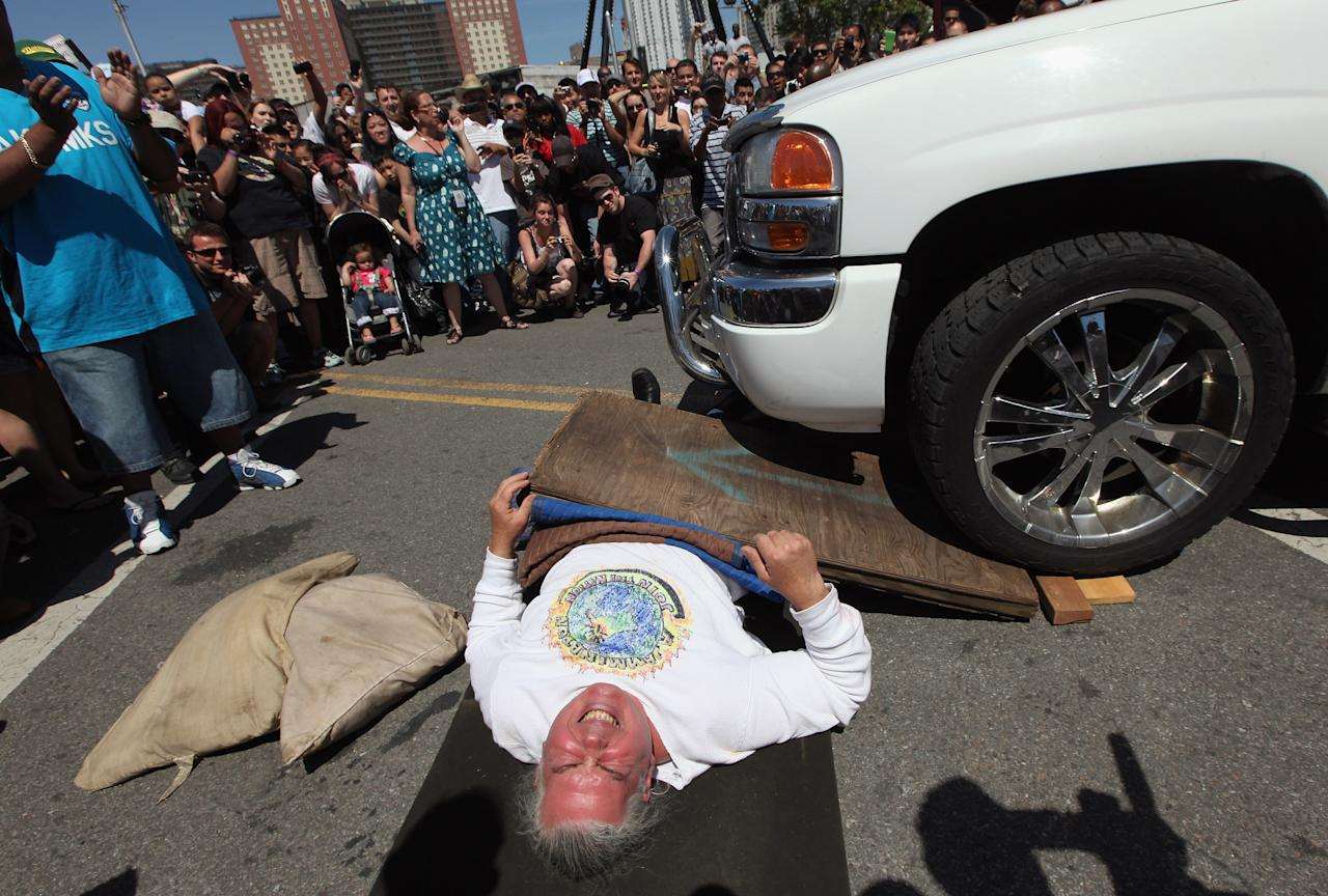 NEW YORK, NY - MAY 20:    A participant reacts after the front wheel of a truck rolled on top of his midsection during the Olde Time Coney Island Strongman Spectacular on May 20, 2012 in New York City. The old fashioned event featured participants who displayed feats of strength including bending wrenches, towing automobiles and lifting fire hydrants.  (Photo by Mario Tama/Getty Images)