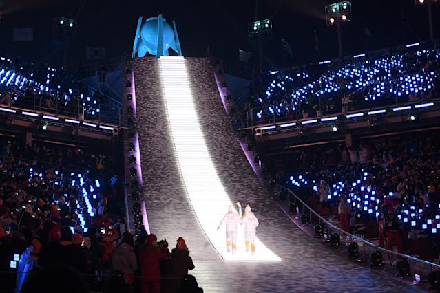 <p>Torchbearers carry the Olympic flame to its cauldron during the Opening Ceremony of the PyeongChang 2018 Winter Olympic Games at PyeongChang Olympic Stadium on February 9, 2018 in Pyeongchang-gun, South Korea. (Photo by Quinn Rooney/Getty Images) </p>