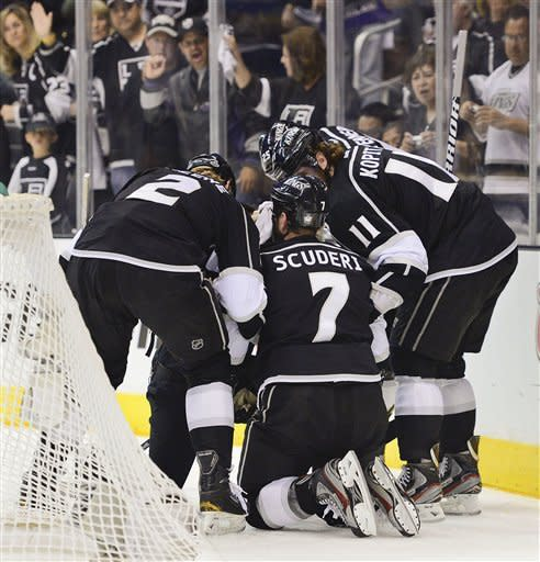 Los Angeles Kings defenseman Rob Scuderi (7) is helped up by teammates after being hit from behind by New Jersey Devils right wing Steve Bernier (18) in the first period, during Game 6 of the NHL hockey Stanley Cup finals, Monday, June 11, 2012, in Los Angeles. (AP Photo/Mark J. Terrill)
