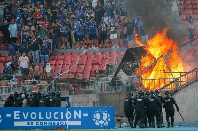 Chile's Riot police disperse Chile's Universidad de Chile supporters that set a fire at the stands during the Copa Libertadores football match against Brazil's Internacional at the National stadium in Santiago, on February 4, 2020. (Photo by JAVIER TORRES / AFP) (Photo by JAVIER TORRES/AFP via Getty Images)
