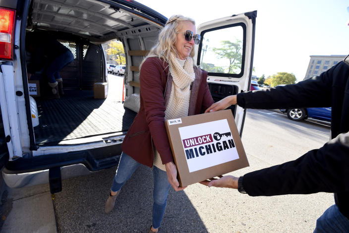 Jill Rechsteiner of Midland helps unload boxes filled with petition signatures as they are delivered by Unlock Michigan to the Michigan Department of State Bureau of Elections in Lansing, Mich., Friday, Oct. 2, 2020. The group is seeking to revoke Governor Gretchen Whitmer's ability to govern by emergency decree. Whitmer, a Democrat, has opposed initiative, saying she has saved lives with the law that lets her unilaterally extend a state of emergency and therefore issue underlying orders to curb COVID-19. (Rod Sanford/Detroit News via AP)