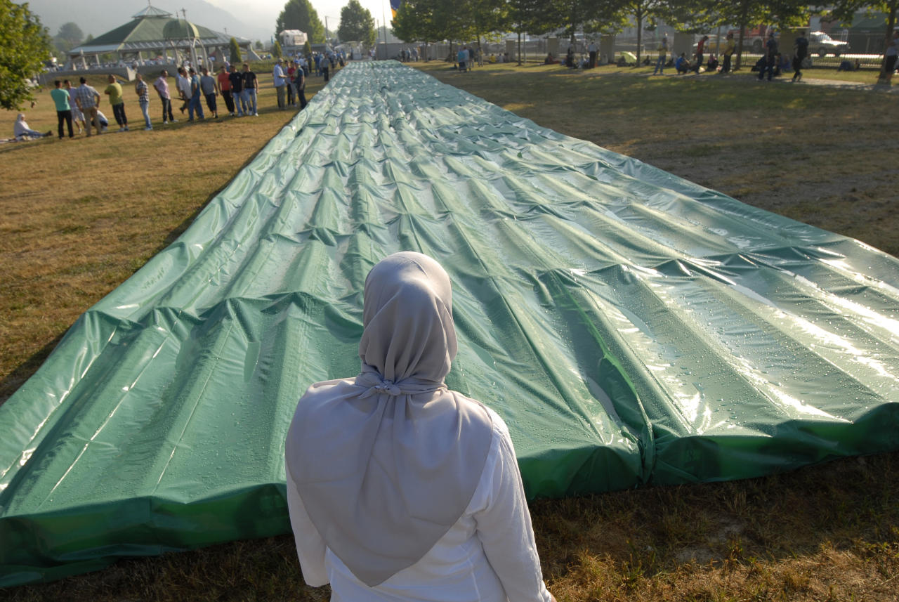 Bosnian Muslim woman prays in the front of the 520 coffins laid out at the Potocari memorial cemetery near Srebrenica, some 160 kilometers east of Sarajevo, Bosnia, Wednesday, July 11, 2012. Thousands gathered in the cemetery for the mass burial of 520 bodies, marking 17th anniversary of the Srebrenica massacre. (AP Photo/Sulejman Omerbasic)