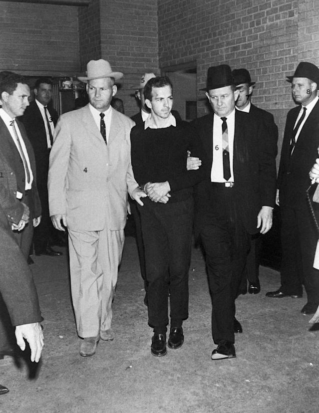 <p>Guards escort Lee Harvey Oswald during a press conference two days after his arrest in conjunction with the assassination of President Kennedy in Dallas, Texas on Nov. 24, 1963. Oswald was shot by local night club owner Jack Ruby during the press conference. (Photo: Corbis via Getty Images) </p>