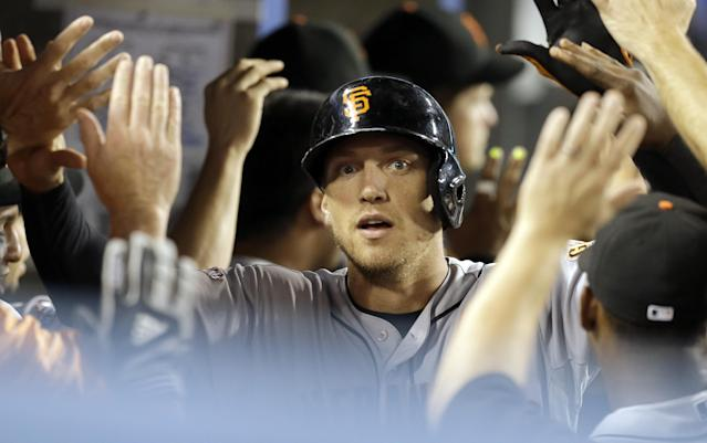 San Francisco Giants' Hunter Pence is congratulated in the dugout on his grand slam against the Los Angeles Dodgers in the fifth inning of a baseball game in Los Angeles Saturday, Sept. 14, 2013. (AP Photo/Reed Saxon)