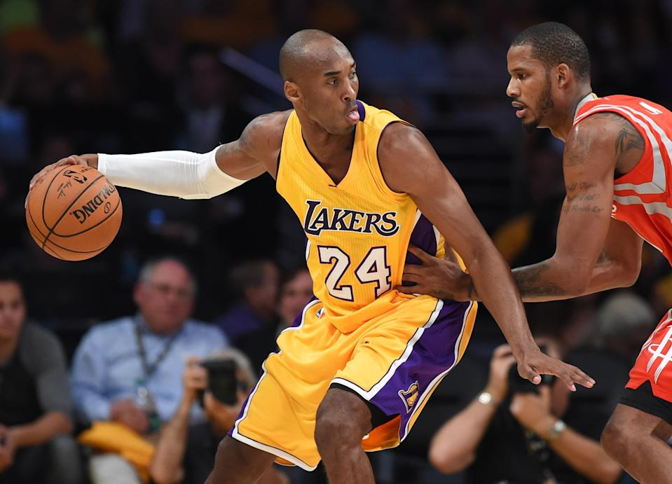 Kobe Bryant (L) of the Los Angeles Lakers moves the ball on court against the Houston Rockets during the Laker's first regular season NBA game, October 28, 2014 at Staples Center in Los Angeles, California (AFP Photo/Robyn Beck)