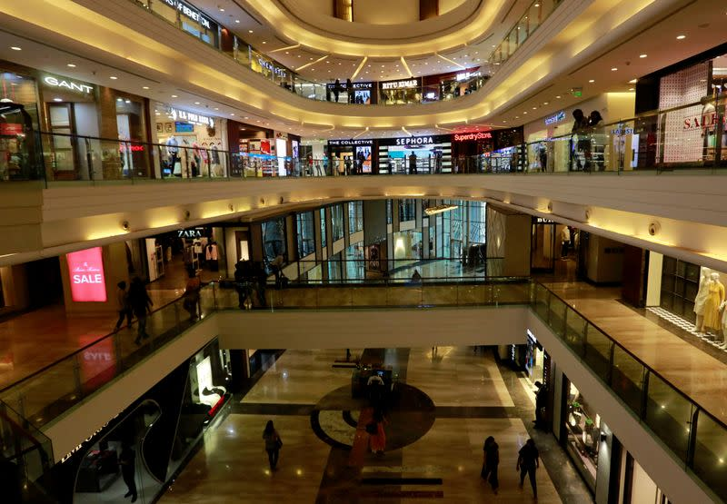 Shoppers walk past stores at a mall in Mumbai