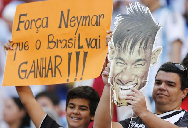 """Fans hold a cutout showing Brazilian player Neymar with a sign that reads in Portuguese '""""Strength Neymar, Brazil will win,"""" before the World Cup quarterfinal soccer match between Argentina and Belgium at the Estadio Nacional in Brasilia, Brazil, Saturday, July 5, 2014. Neymar, the biggest football star in Brazil, was ruled out of the rest of the tournament after fracturing his third vertebra during Friday's 2-1 quarterfinal win over Colombia. (AP Photo/Eraldo Peres)"""