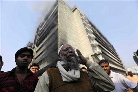 An employee cries in front of a Standard Group garment factory which was on fire in Gazipur November 29, 2013. There were no reports of casualties in the fire. REUTERS/Andrew Biraj