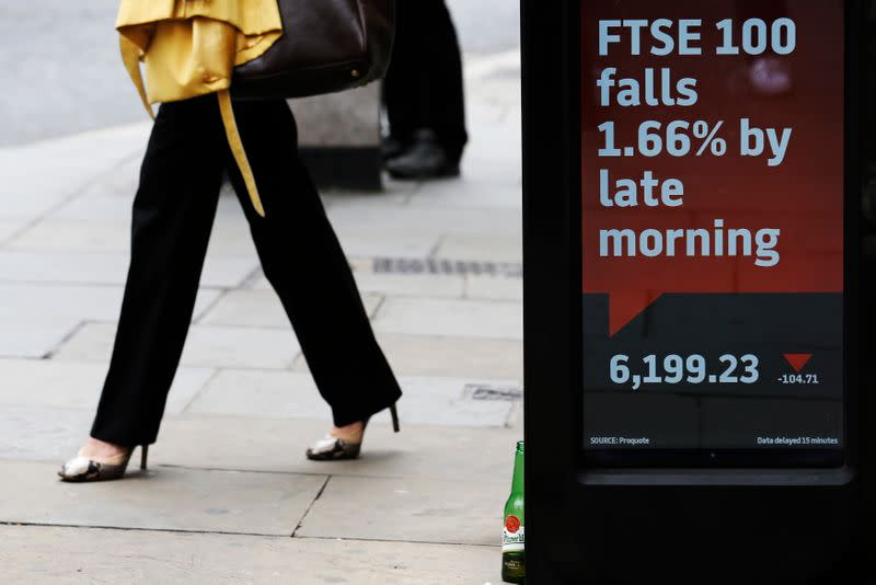 A woman passes an electronic sign showing the FTSE 100 index, in the City of London