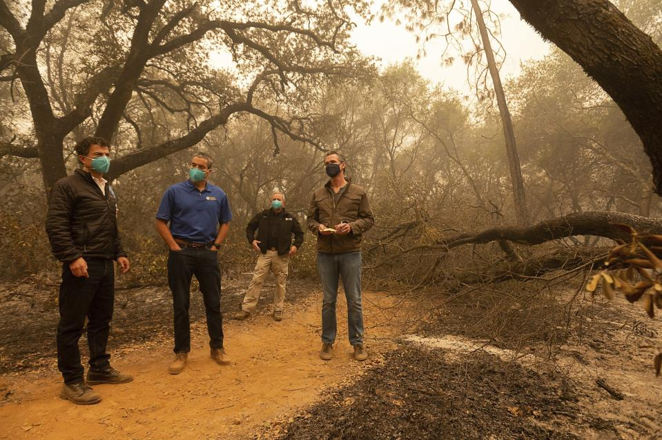 "California Gov. Gavin Newsom, right, takes notes as he tours the North Complex Fire zone with California Secretary for Environmental Protection Jared Blumenfeld, left, and California Secretary for Natural Resources Wade Crowfoot, second left, in Butte County on Friday, Sept. 11, 2020, outside of Oroville, Calif. Newsom toured the fire-ravaged region Friday and strongly asserted that climate change was evident and pledged to redouble efforts to ""decarbonize"" the economy. (Paul Kitagaki Jr./The Sacramento Bee via AP, Pool)"