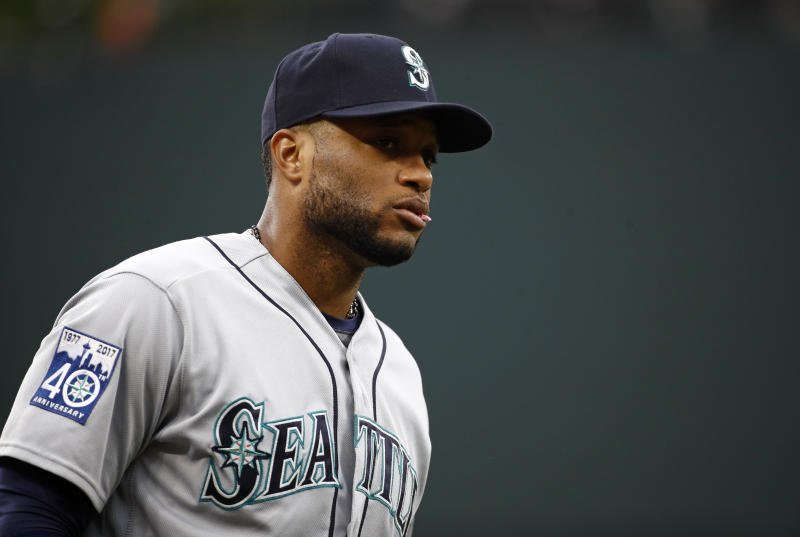 FILE - In this Aug. 28, 2017, file photo, Seattle Mariners' Robinson Cano walks on the field before a baseball game against the Baltimore Orioles in Baltimore. Cano has been suspended 80 games for violating baseball's joint drug agreement, the league announced Tuesday, May 15, 2018. (AP Photo/Patrick Semansky, File)