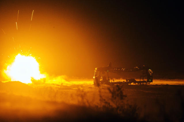 <p>A rocket fired by U.S. soldiers from Dragon Troop of the 3rd Cavalry Regiment explodes next to a destroyed bus at operating base Gamberi in the Laghman province of Afghanistan Dec. 31, 2014. (Photo: Lucas Jackson/Reuters) </p>