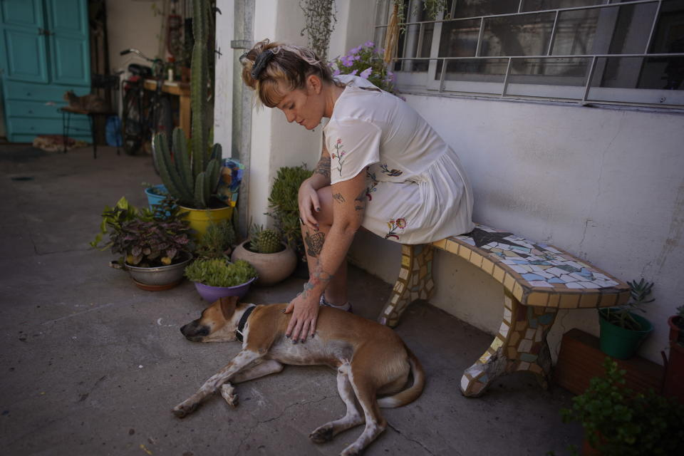 """Tamara Grinberg, 32, pets her dog at her home in San Martin, Buenos Aires province, Argentina, Friday, Jan. 22, 2021. Grinberg who had a clandestine abortion in 2012 said very few people helped her. """"Today there are many more support networks ... and the decision is respected. When I did it, no one respected my decision."""". (AP Photo/Victor R. Caivano)"""