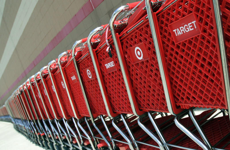 In this July 28, 2012 photo, shopping carts sit parked outside a Target store in Marlborough, Mass. Target is reporting that net income for the second quarter was unchanged, as the retailer gets ready for its upcoming move into Canada. But the retailer saw solid spending in the quarter and in a sign of confidence, the cheap chic discounter raised its earnings outlook. Target posted earnings Wednesday, Aug. 15, 2012 of $704 million, or $1.06 per share in the period ended July 30. That compares with $704 million or $1.03 per share, in the year ago period.  (AP Photo/Bill Sikes)