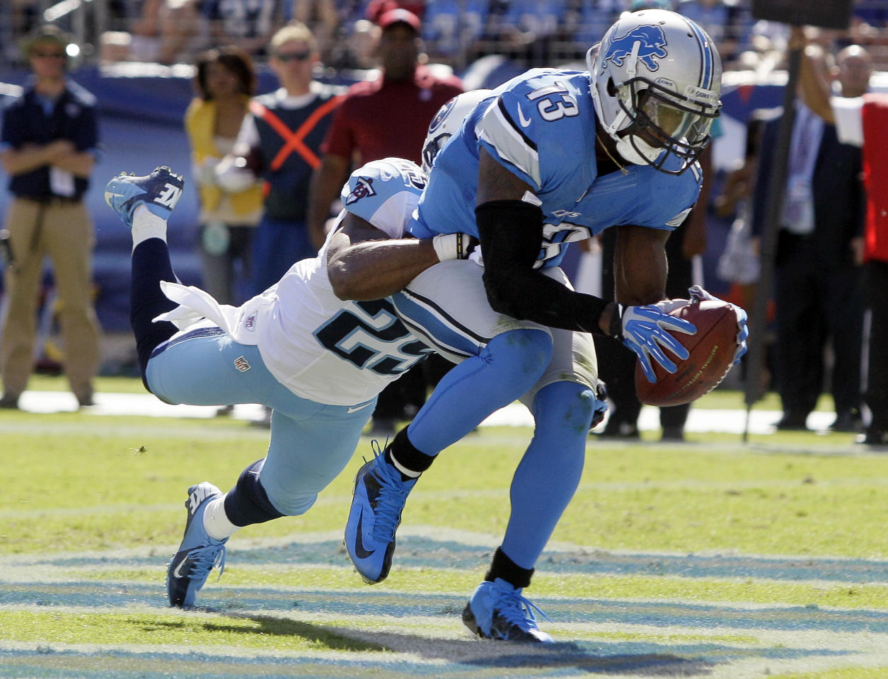 Detroit Lions wide receiver Nate Burleson (13) catches a touchdown pass as he is defended by Tennessee Titans cornerback Ryan Mouton (29) in the fourth quarter of an NFL football game on Sunday, Sept. 23, 2012, in Nashville, Tenn. (AP Photo/Wade Payne)