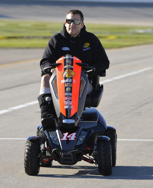 In this Sept. 13, 2013, photo, Tony Stewart drives a motorized scooter before qualifications for the NASCAR Sprint Cup Series auto race at Chicagoland Speedway in Joliet, Ill. Stewart fractured his tibia and fibula in sprint car race in Iowa the previous month. Stewart and Kasey Kahne are entering next month's Chili Bowl Nationals in honor of the late racer Jason Leffler. Kahne will drive a car entered in combination with Stewart; Leffler's girlfriend, Julianna Patterson; and former father-in-law, Bob East, in the Jan. 14-18 race at the Tulsa Expo Center in Oklahoma. (AP Photo/Nam Y. Huh)