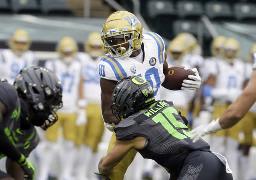 UCLA's Demetric Felton, left, is tackled by Oregon's Bennett Williams during the first quarter of an NCAA college football game Saturday, Nov. 21, 2020, in Eugene, Ore. (AP Photo/Chris Pietsch)