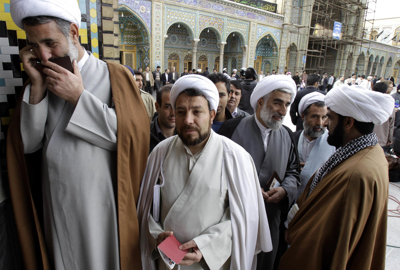 Mojtaba Zolnouri, a former top official with Iran's elite Revolutionary Guard, left, talks on his mobile phone as the other clerics queue to cast their ballots during the parliamentary elections at Masoumeh shrine in the city of Qom, 78 miles (125 kilometers) south of the Tehran, Iran, Friday, March 2, 2012. The balloting for the 290-member parliament is the first major voting since the disputed re-election of President Mahmoud Ahmadinejad in June 2009 and the mass protests and crackdowns that followed.. (AP Photo/Kamran Jebreili)