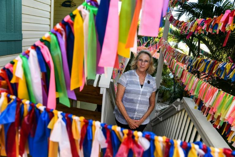 Cathy Tobias, 67, poses in her courtyard which has turned into a colorful memorial for Covid-19 victims