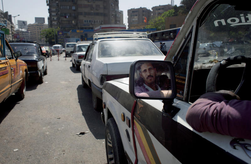 An Egyptian driver with his face reflected in a side mirror queues for fuel near an overcrowded gas station in Cairo, Egypt, Wednesday. Egypt has been increasingly knocking on doors around the world seeking billions to fill rapidly draining coffers. But not everyone is eager to give, and economists fear that quick injections of cash only let the government put off painful economic reform. (AP Photo/Nasser Nasser)