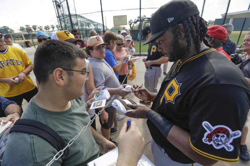 Pittsburgh Pirates' Josh Bell, right, gives an autograph to Joey Alejos, left, after a spring training baseball workout Monday, Feb. 17, 2020, in Bradenton, Fla. (AP Photo/Frank Franklin II)