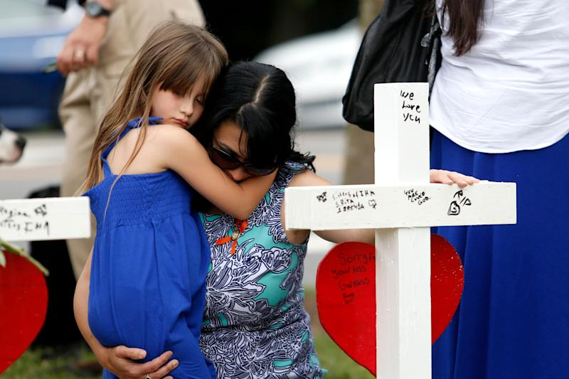 Del. Kelly Fowler holds her daughter Sophie, 6, in front of the row of crosses at the memorial located by Building 11 of the Virginia Beach Municipal Center, June 2, 2019, in Virginia Beach, Va. Twelve crosses were placed at the memorial to honor the 12 victims of the mass shooting that took place at the center several days earlier. (Photo: Sarah Holm/The Virginian-Pilot via AP)