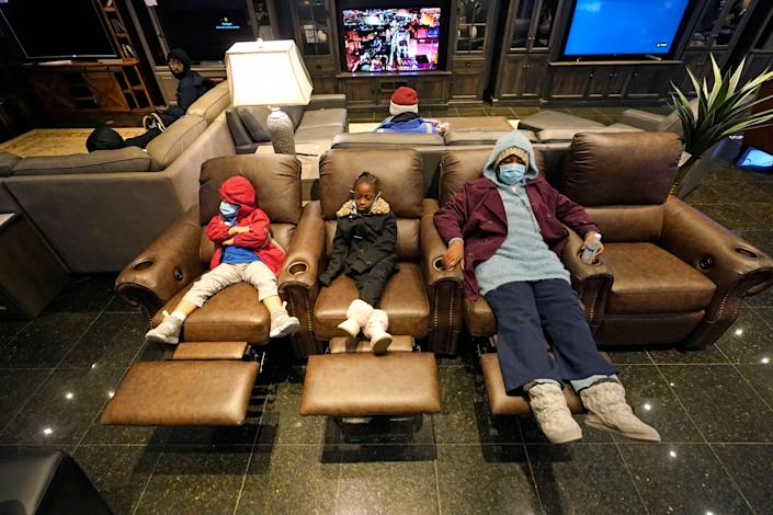Joecyah Heath, left, Morning Day, center, and Jenesis Heath rest in recliners at a Gallery Furniture store which opened as a shelter Wednesday, Feb. 17, 2021, in Houston. Millions in Texas still had no power after a historic snowfall and single-digit temperatures created a surge of demand for electricity to warm up homes unaccustomed to such extreme lows, buckling the state's power grid and causing widespread blackouts. (AP Photo/David J. Phillip) (AP)