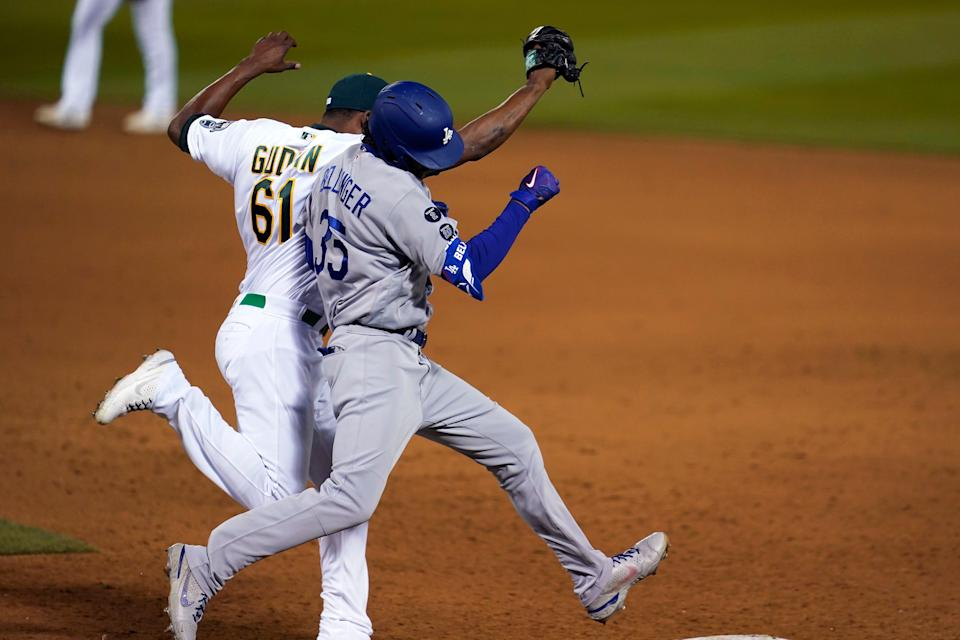 Oakland Athletics pitcher Reymin Guduan (61) makes contact with Los Angeles Dodgers' Cody Bellinger on Bellinger's single during the ninth inning of a baseball game in Oakland, Calif., Monday, April 5, 2021. Guduan and Bellinger both left the game after the play. (AP Photo/Jeff Chiu)