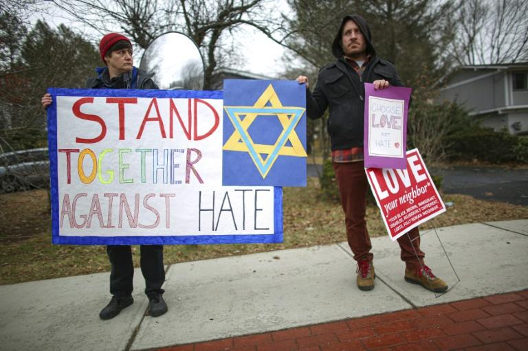 People hold signs of support near the house of Rabbi Chaim Rottenberg in Monsey, New York after the latest attack against Jewish targets (AFP Photo/Kena Betancur)